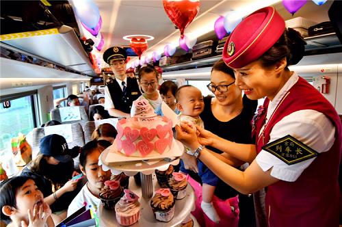 """天津客运段津京沪车队乘务员与旅客在北京南至上海虹桥G1次列车上共同为""""复兴号""""一周岁切蛋糕庆生"""